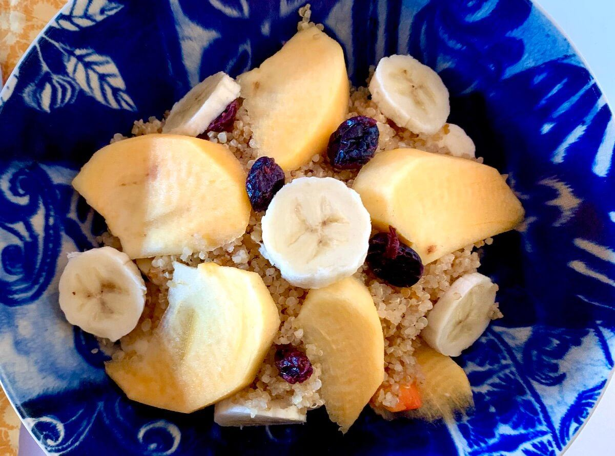 Bowl of quinoa with persimmon, banana and dried cranberries