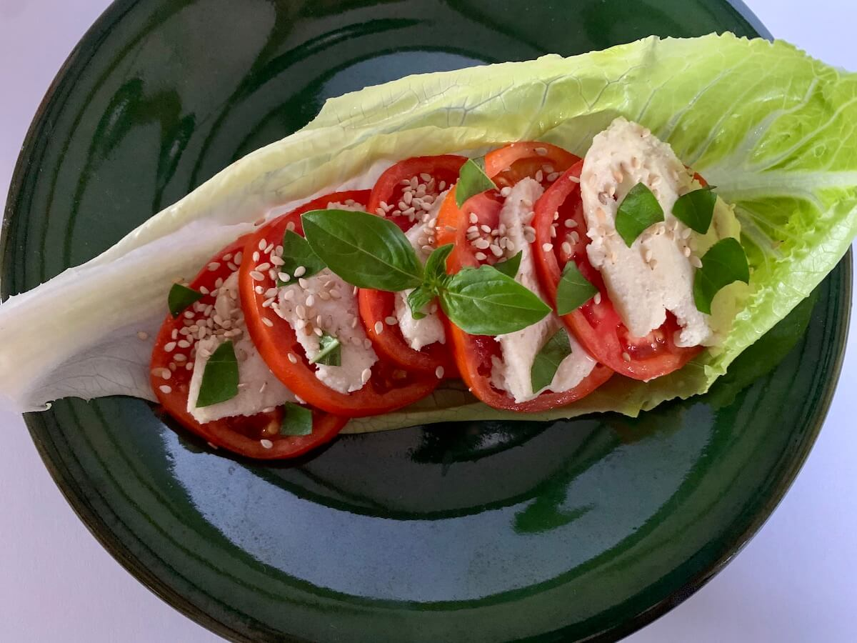 Vegan Caprese salad served on a lettuce leaf