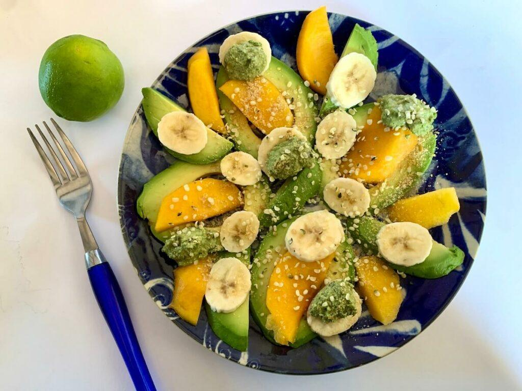 Plate of avocado & fruit topped with hemp seed