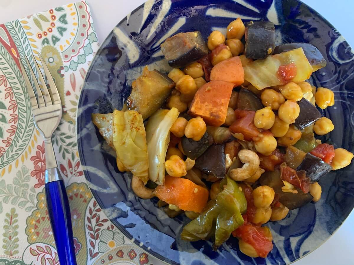 Plate of leftover chickpeas, sweet potato, cabbage and other veggies for breakfast