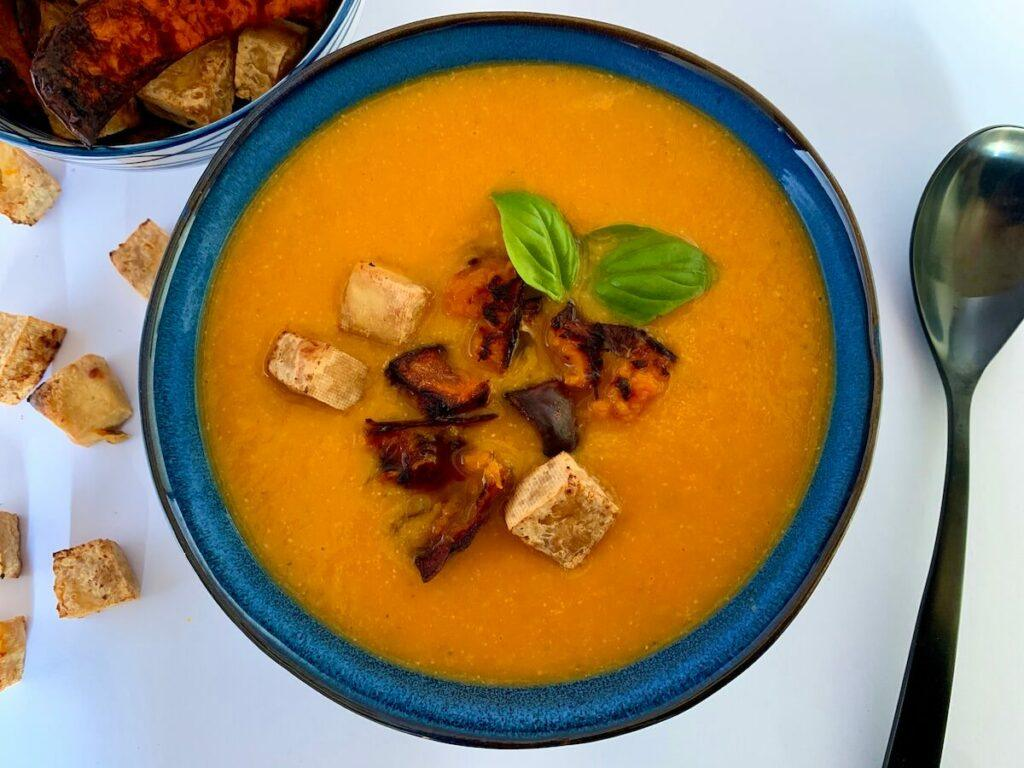 Bowl of roasted pumpkin soup with tofu croutons and pumpkin chips on top