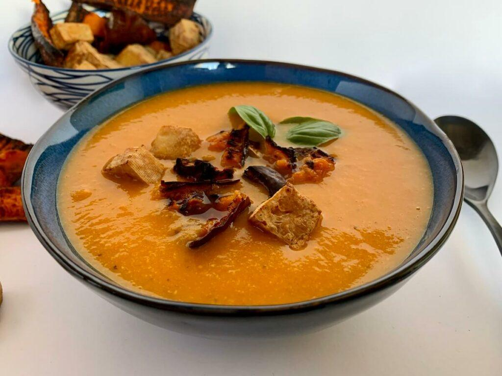 Bowl of roasted pumpkin soup with tofu croutons on top