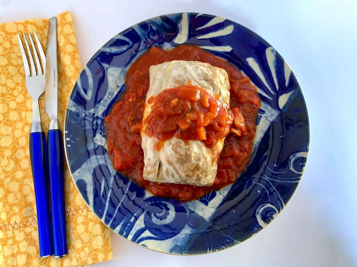 Vegan stuffed cabbage roll with tomato sauce served on a blue plate