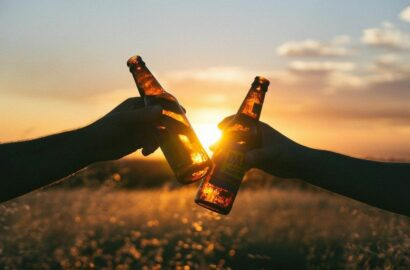 Two bottles raised against the sunset in a cheers movement