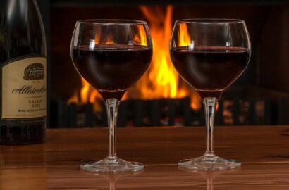 Two glasses of red wine in front of the fire