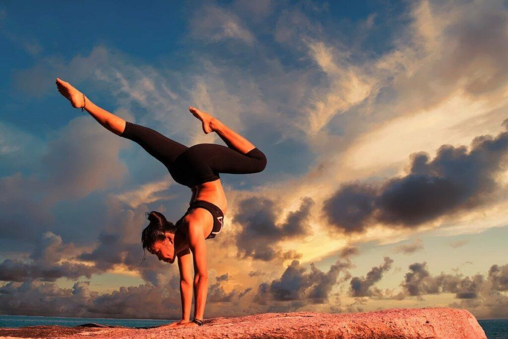Woman doing yoga on a rock, with sky as a backdrop