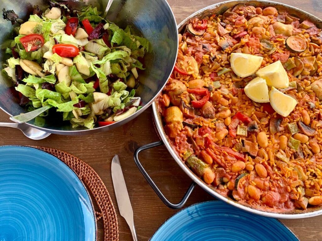 Vegan paella in a pan and a bowl of mixed salad