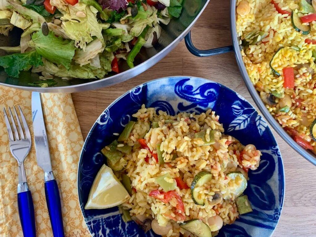 Bowl of vegetable paella with lemon and salad